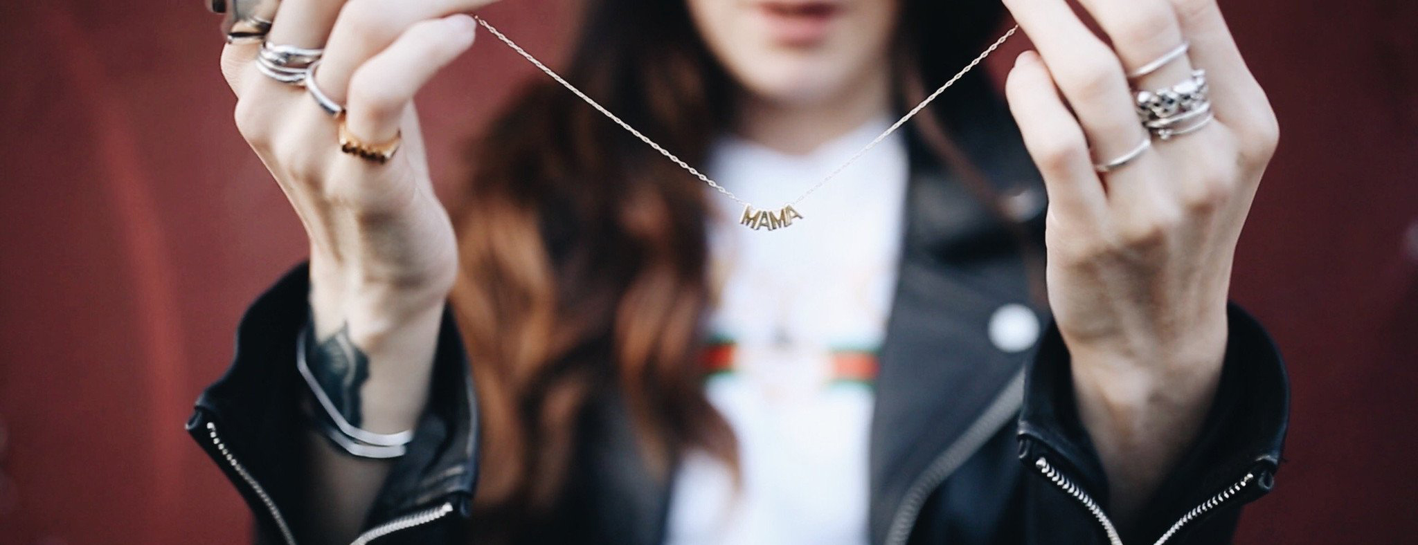 Cult of Youth founder Kelly Seymour holding her signature Mama chain